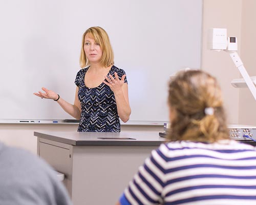 Professor teaching class at a Christian college school of education.