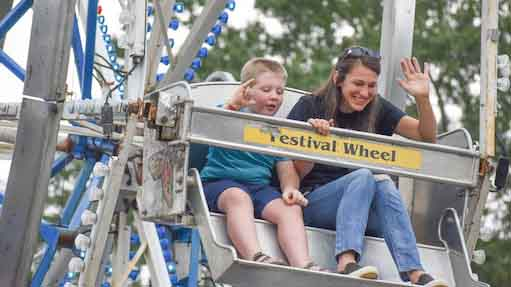 SWU alumna Kelly Tegen waves from a ferris wheel at the 2019 Homecoming celebrating alumni experiences at this Christian college.